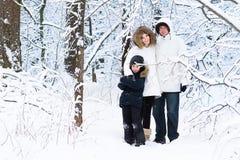 走在多雪的森林里的愉快的幼小三口之家 免版税库存图片