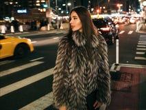 走在夜城市街道上的华美的端庄的妇女穿假毛皮夹克和拿着看对边的袋子 免版税库存图片