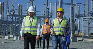 走在太阳驻地平台的小组工程师 免版税库存照片