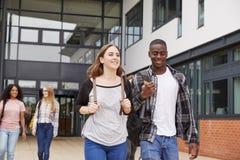走在学院大厦之外的小组学生 免版税库存照片