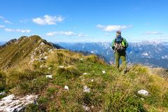 走在它上面山的人徒步旅行者反对天空蔚蓝 库存图片