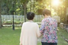 走在室外公园的背面图亚裔年长妇女 免版税库存照片