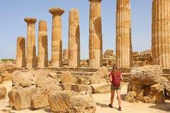 走在寺庙阿哥里根托,西西里岛的谷的年轻女人 旅客女孩在意大利南部参观希腊寺庙 库存照片