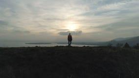 走在小山的一个远足人到湖在日落 股票录像