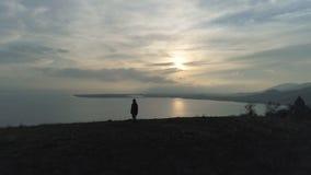 走在小山的一个远足人到湖在日落 影视素材