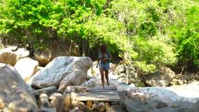 走在山河的桥梁的旅游妇女,当夏天高涨时 走在热带的河桥梁的少妇 影视素材