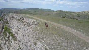 走在山的两个女孩在印象深刻的峭壁边缘在克里米亚 股票视频