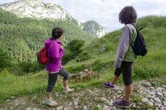 走在山的两个妇女远足者 免版税库存图片
