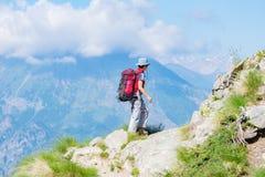 走在山的供徒步旅行的小道的背包徒步旅行者 夏天冒险在阿尔卑斯的暑假 旅行癖人旅行的骗局 库存图片