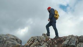 走在山的峰顶的人在慢动作,挪威,欧洲的日落 佩带夹克、红色帽子和黄色 股票录像