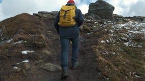 走在山的峰顶的人在慢动作,挪威,欧洲的日落 佩带夹克、红色帽子和黄色 影视素材