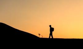 走在山的背包徒步旅行者 免版税库存照片