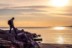 走在岩石峭壁的旅行家反对海、日出或者日落 库存图片
