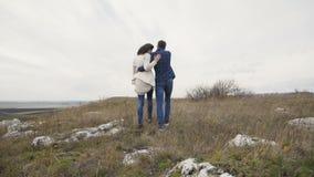 走在岩石的可爱的夫妇后面看法在大风天 4K 股票录像