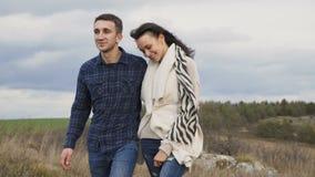走在岩石的可爱的夫妇在大风天 4K 股票录像
