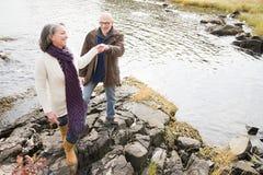 走在岩石的成熟夫妇 库存图片