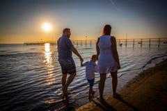 走在岸的愉快的家庭 免版税库存图片