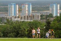 走在工业建筑用起重机背景的Mamaev小山和修造在伏尔加格勒的人们 库存图片