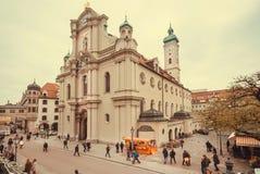 走在市场和18世纪哥特式样式Heiliggeistkirche教会附近的家庭 库存图片