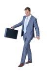 走在带着手提箱的平衡的商人 免版税库存照片