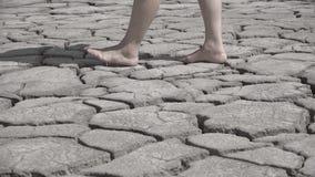 走在干旱和破裂的土壤,光秃的费的脚去在干燥地面,概念性 股票视频