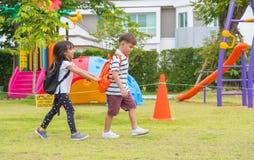 走在幼儿园PR的操场的两个孩子小学生 免版税库存照片