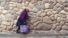 走在库斯科,秘鲁的一名老未认出的秘鲁妇女 免版税库存照片