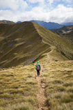 走在开普勒轨道的一个高山部分的妇女远足者 免版税库存照片