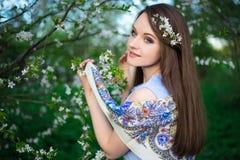 走在开花的夏天庭院里的愉快的少妇 图库摄影