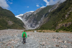 走在弗朗兹约瑟夫冰川的妇女背包徒步旅行者 图库摄影