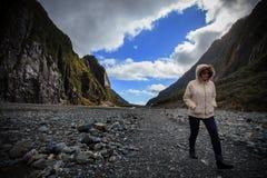 走在弗朗兹约瑟夫冰川足迹重要旅行的目的地的年轻旅行的妇女在南岛新西兰 免版税库存照片