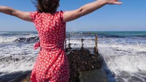 走在往风雨如磐的海的码头的年轻愉快的妇女有涂她的手的波浪的分开摆在 强风和波浪sp 股票视频
