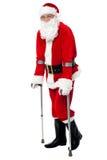 走在拐杖帮助下的圣诞老人 免版税库存图片