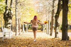 走在拿着五颜六色的叶子的秋天时间的公园的可爱的少妇 免版税库存照片