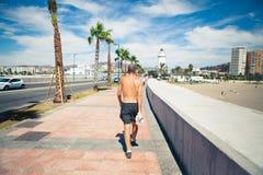 走在散步的老人在海岸 免版税图库摄影