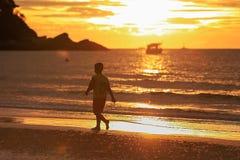 走在日出的海滩的年轻人剪影 库存照片