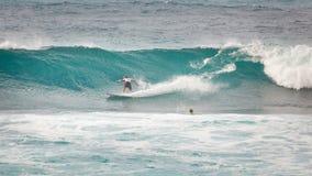 走在日落海滩夏威夷的冲浪者 库存图片