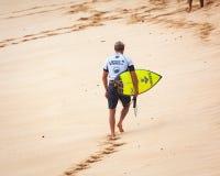 走在日落海滩夏威夷的冲浪者 库存照片