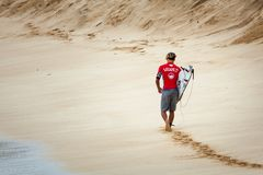 走在日落海滩夏威夷的冲浪者 免版税图库摄影