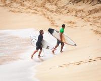 走在日落海滩夏威夷的赞成冲浪者 库存图片