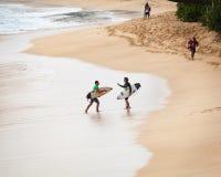 走在日落海滩夏威夷的赞成冲浪者 免版税库存图片