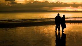走在日落的一个海滩的年长夫妇 免版税库存照片