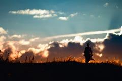 走在日落的女孩的剪影 免版税库存照片