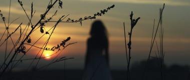 走在日落的女孩 免版税库存图片