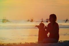 走在日落的母亲和小女儿 库存照片