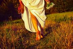 走在日落的美丽的女孩 库存照片
