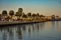 走在日落背景的木板走道的人们在佛罗里达的历史的海岸的奥尔德敦 免版税图库摄影
