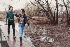 走在早期的春天的年轻愉快的爱恋的夫妇生活方式接近的室外画象  免版税库存照片