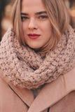 走在时髦的温暖的成套装备的年轻美丽的妇女画象在晴朗的秋天天在公园、佩带的桃红色外套和被编织的妇女发网 免版税库存照片