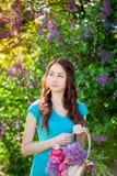 走在春天有花篮子的庭院的美丽的妇女  免版税库存图片